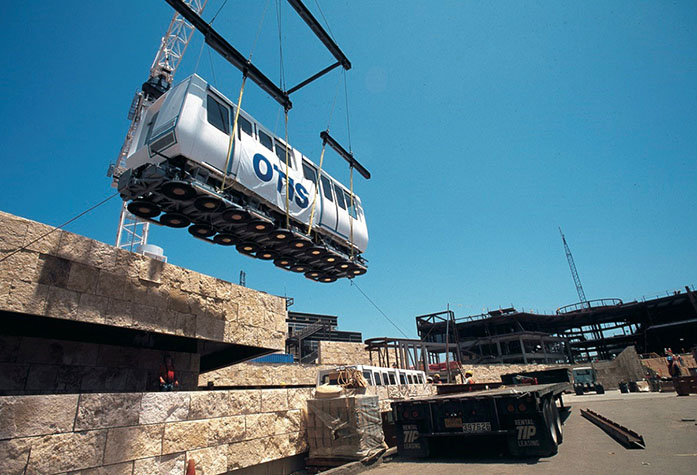 A crane lowers a tram onto the tracks during the construction of the Getty Center in late 1994.