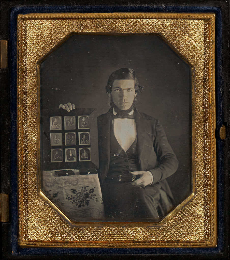 Portrait of a Daguerreotypist Displaying Daguerreotypes and Cases