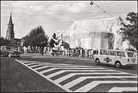 A black-and-white photograph documents a large building that has been fully wrapped in white fabric and twine, transforming it into a work of art thronged by people. The photograph was taken in the middle of a crosswalk stretching toward the building, and a taxi enters the frame on the right side.