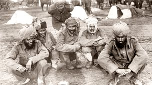 Black and white photo of men sitting on ground with head wraps.