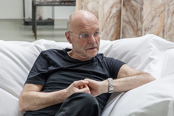 Middle-aged white man with glasses (artist Anselm Kiefer) sits on a large cushion, interlocking his fingers as he looks off-frame to his left.