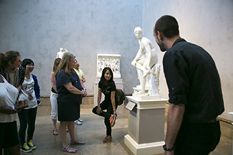 A visitor mimics the pose of a sculpture in a gallery at the Getty Center.