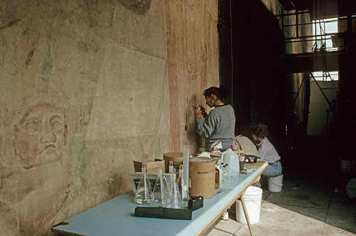 conservators working on mural