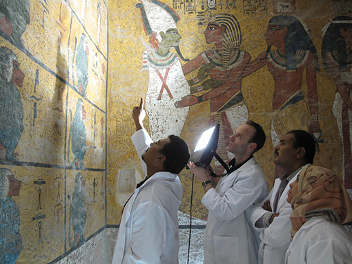 Conservators examining the wall paintings on the west wall of the burial chamber.