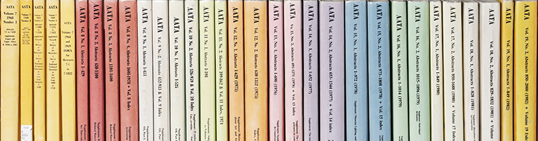 Image of the spines of multiple volumes of the printed AATA publiation