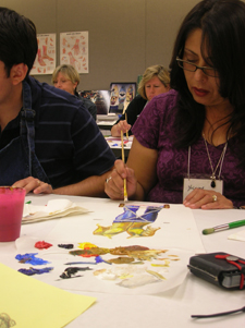 A teacher paints a work of art during a hands-on workshop.