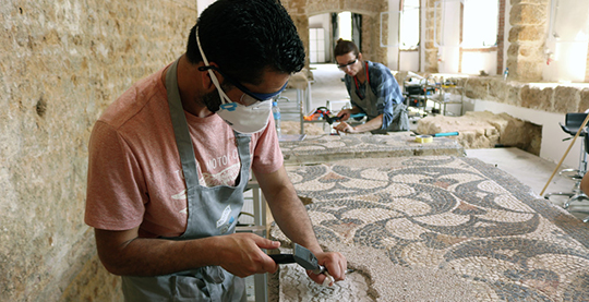 A MOSAIKON training participant removes mortar on a mosaic in Tipasa, Algeria.