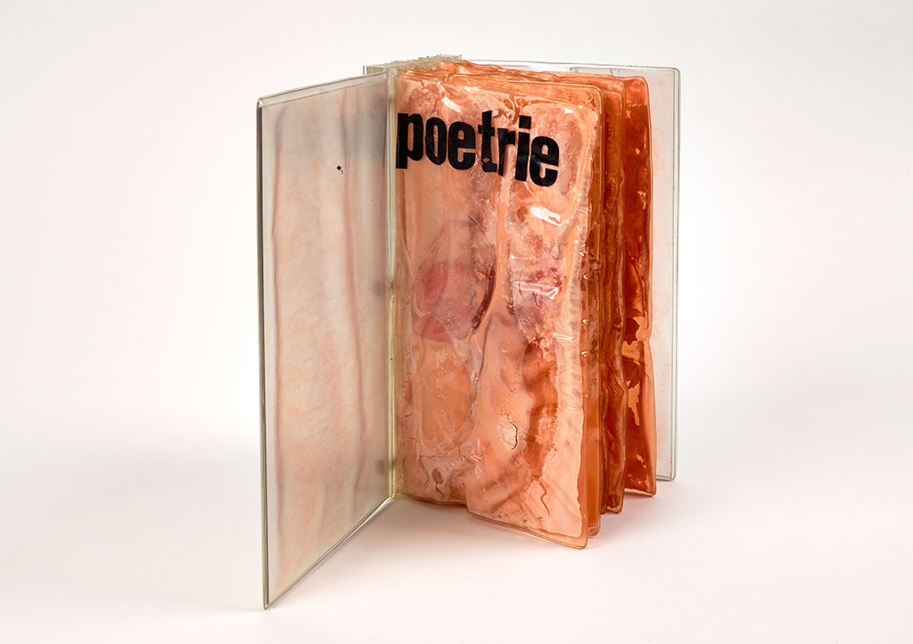 A book with a Plexiglas exterior stands upright with the cover open to reveal distressed pages of plastic-sealed cheese. The title poetrie appears in lowercase letters across the top of the first page.