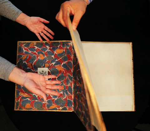 Animation of hands opening a folding plate of the Facade of the Church of the Invalides from a bound volume of 17th century prints