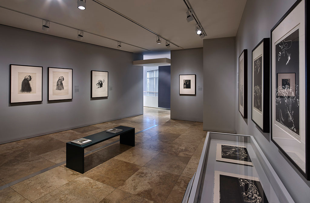 A view of the exhibition installed in gallery. Framed works line the walls and placed in a glass case. Related publications rest on a bench center of the gallery.