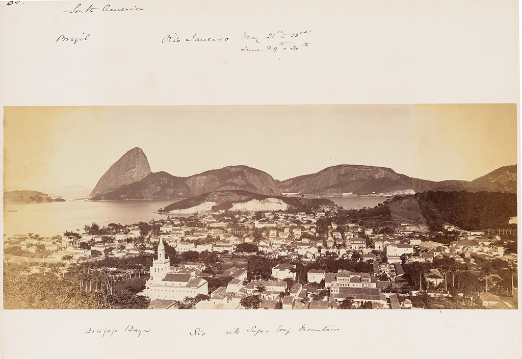 A panoramic, black-and-white photograph of Rio de Janeiro with the city center in the foreground and the bay and its surrounding mountains in the background
