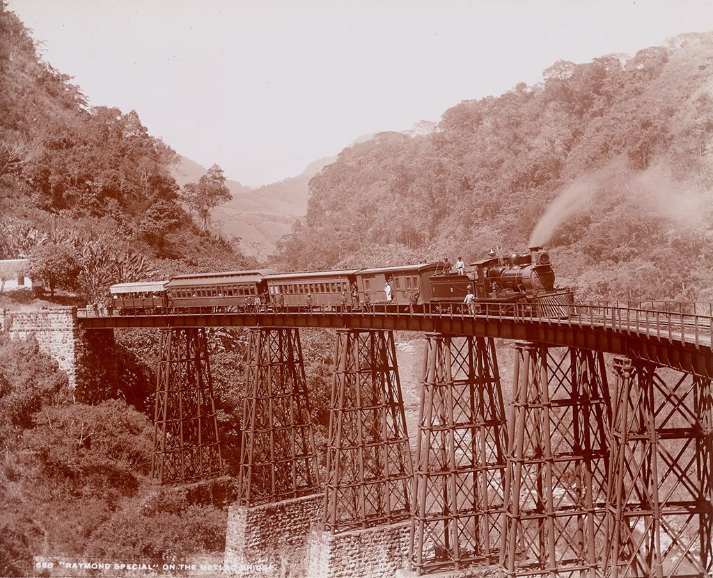 A black-and-white photograph documents a steam locomotive as it traverses a dramatically curving, cast-iron bridge looming over a deep ravine