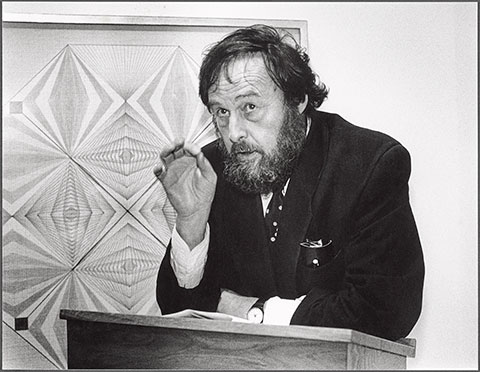 A black-and-white photograph documents the curator Harald Szeemann, a thickly bearded man with disheveled hair, standing behind a podium, delivering a lecture in front of an abstract geometric drawing by the psychic and healer Emma Kunz.