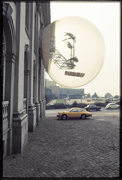 A color photograph documents an artwork by a collective of avant-garde architects: an oversized, clear bubble protruding from the side of a stone building, containing two palm trees attached to a silver gridded structure. A yellow sports car is parked on the sidewalk underneath it.