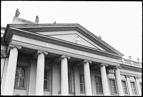 A black-and-white photograph documents a performance: the artist James Lee Byars is in a white suit, standing on the ledge of a large columned building with his back turned toward the camera.