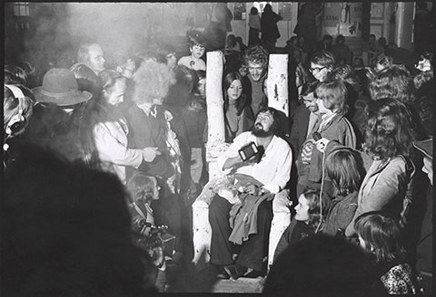 A black-and-white photograph documents the curator Harald Szeemann, a heavily bearded man in his thirties, sitting on a wooden throne in the middle of a crowd with a passport in his hand.