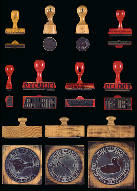 Bottom and side views of eleven of Harald Szeeman's rubber stamps are arranged in three rows.
