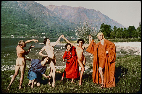 A color photograph documents a troupe of early 20th-century dancers in a grassy meadow in front of a towering mountain; three are nude and three are wearing vibrant robes as they pose with their arms raised and hands interlocking.