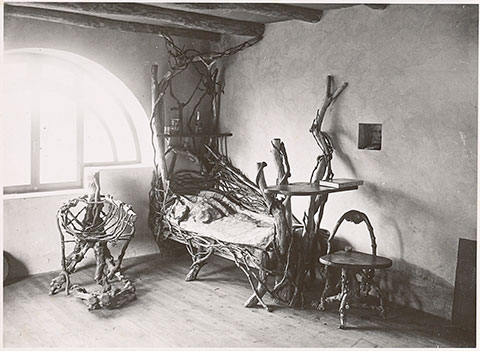 A black-and-white photograph documents a spare room with thick ceiling beams and a light-filled, half-round window. Pushed up against the wall near the window are two low chairs and a bed made from intertwined tree branches.