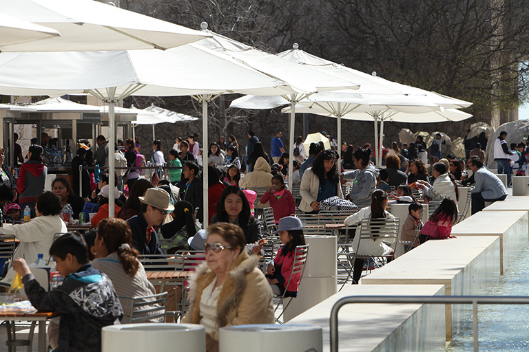 On a sunny day, visitors eat and socialize under the umbrellas lining the fountain in the Museum Plaza.